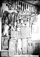 A view of the museum display: stone gravestones and architectonic members below, iron and bronze ware above on the museum wall, and collection of clay weights under the ceiling
